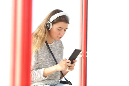 Serious teenage girl listening to music wearing wireless headphones and using smart phone in a bus stop