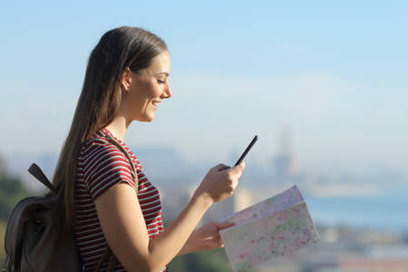 Happy tourist woman with backpack looking for indications on her mobile phone while holding a map