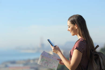 Side view portrait of a young woman with backpack and map checking indications on her smart phone