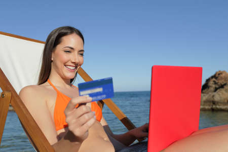 Happy tourist in orange bikini buying online with credit card on her red laptop at the beach Stockfoto