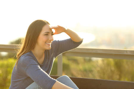 Happy woman looking away with hand on her forehead sitting at the park bench at sunset Stockfoto