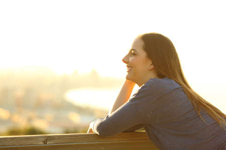 Side view portrait of a happy woman looking away on a sunny terrace with city views at sunset