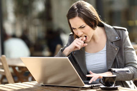 Angry girl pressing button frustrated using her laptop on a coffee shop terrace