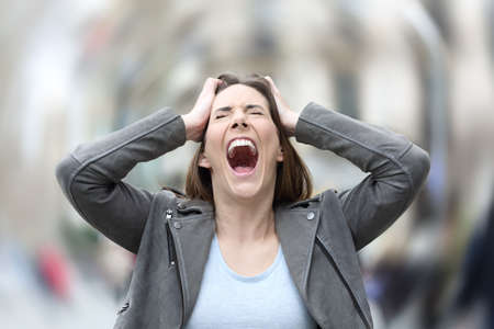 Front view portrait of a stressed woman screaming desperate suffering anxiety attack grabbing her head on city street