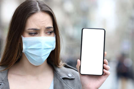 Front view portrait of a scared girl with protective mask preventing contagion looking at her blank smart phone screen