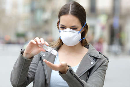 Portrait of a serious girl wearing protective mask applying sanitizer hand rub preventing contagion on city street