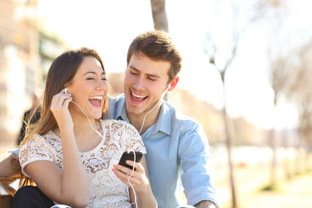 Happy couple singing together listening to music from smart phone sharing earphones sitting on a bench in a park