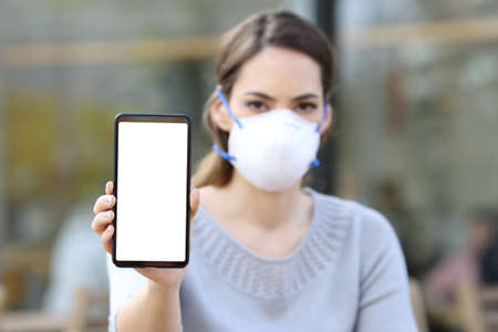 Front view portrait of a serious woman with protective mask showing smart phone with blank screen in a coffee shop Stock Photo