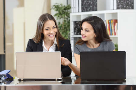 Front view portrait of a businesswoman helping to her colleague at office using laptops