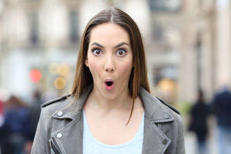 Front view portrait of surprised woman looking at camera with mouth and eyes wide open on a city street