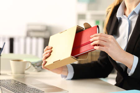 Close up of executive woman hands unboxing package delivery with agenda at the office