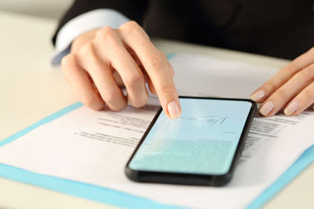 Close up of executive woman hands signs contract on smart phone with finger sitting on a desk Foto de archivo