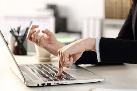 Close up of angry woman executive hands pressing hard laptop button sitting on a desk at the office 版權商用圖片