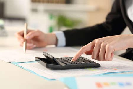 オフィスの机の上で電卓で計算するエグゼクティブウーマンの手のクローズアップ
