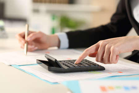 Close up of executive woman hands calculating with calculator on a desk at the office