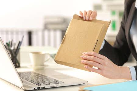オフィスの机の上に配達パッケージを開くエグゼクティブ女性の手のクローズアップ