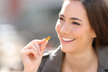 Close up of a happy woman looking away taking vitamin pill outdoor