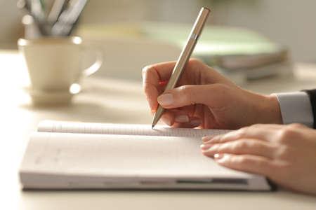 Gros plan des mains d'une femme d'affaires écrivant des notes sur l'ordre du jour la nuit au bureau