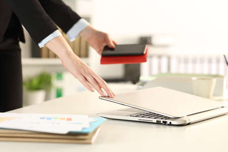 Close up of executive hands leaving office closing laptop taking phone and agenda Foto de archivo