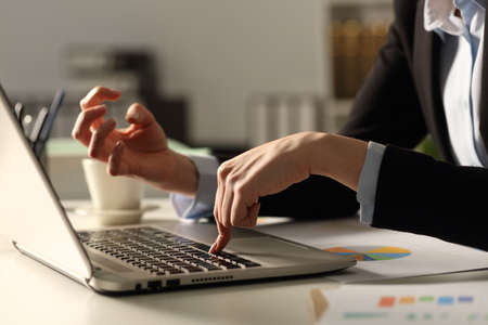 Close up of angry executive woman hands pushing keybord button at night in the office