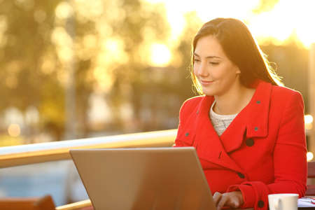 Happy woman reading on laptop at sunset sitting on a balcony