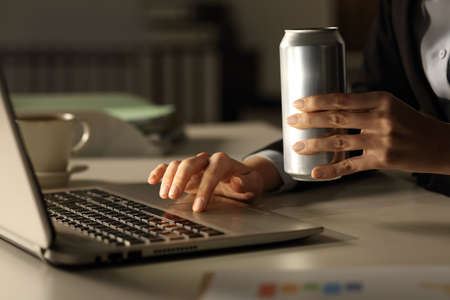 Close up of executive woman hands with laptop holding energy drink can at night in the office Banque d'images