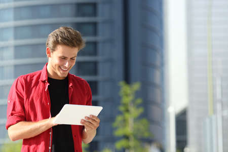 Happy man standing in the street using tablet in a city business area Stockfoto