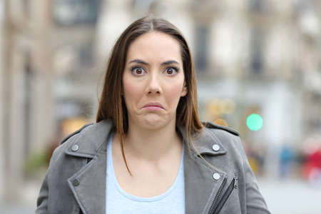 Front view portrait of a confused young woman looking at camera in the street
