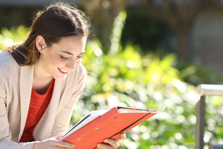 Happy student girl with folder and notebook studying in a park on a sunny day Imagens