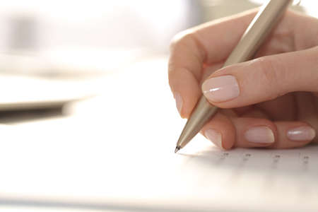 Close up of woman hand filling out form with pen on a desk Banque d'images