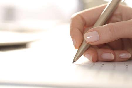 Primo piano della mano della donna che compila il modulo con la penna su una scrivania Archivio Fotografico