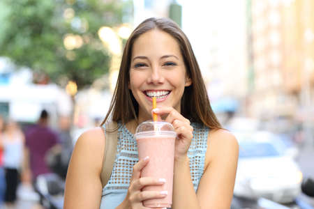 Front view portrait of a happy girl looking camera drinking milkshake in the street Stockfoto