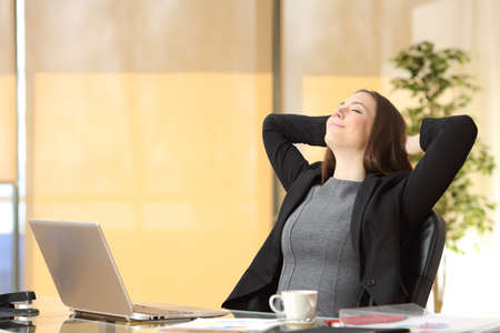 Relaxed executive woman breathing fresh air with arms on head on a desk at the office
