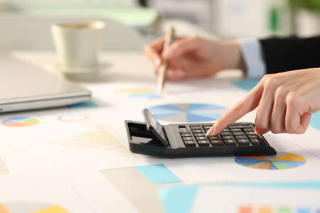 Close up of executive woman hand calculating with calculator comparing graphs sitting on a desk in the office