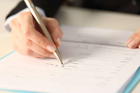Close up of executive woman hand filling form checking yes checkbox sitting on a desk Фото со стока