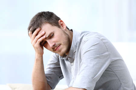 Sad worried man complaining sitting alone on a couch at home