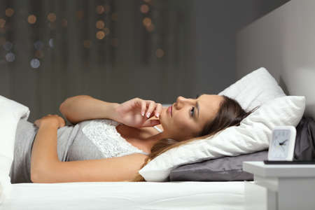 Pensive serious woman thinking lying on the bed in the night at home