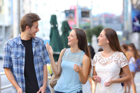 Happy group of three friends laughing and talking in the street
