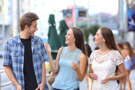 Glückliche Gruppe von drei Freunden, die auf der Straße lachen und reden