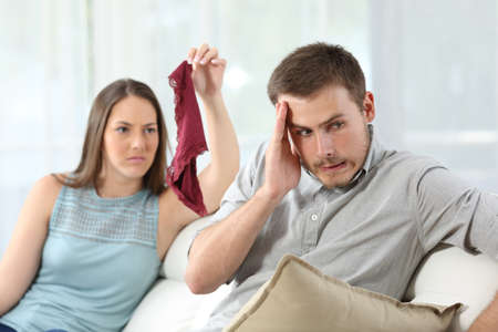 Disloyal cheater boyfriend caught by girlfriend showing underwear of another girl on a couch at home