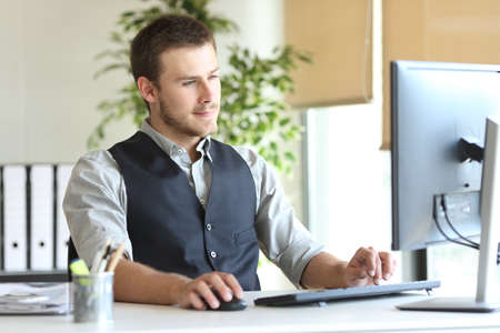 Concentrated executive man using computer sitting on a desk at the office