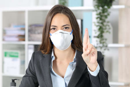 Front view of executive woman with protective mask crossing fingers looking at camera at office