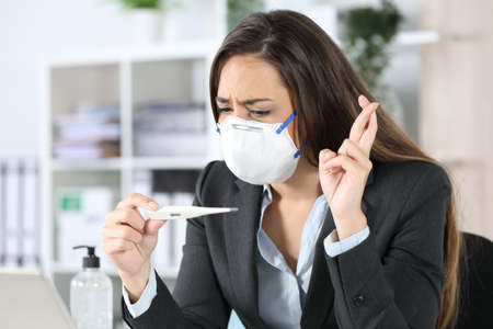 Worried executive woman with protective mask looking at thermometer result crossing fingers at the office