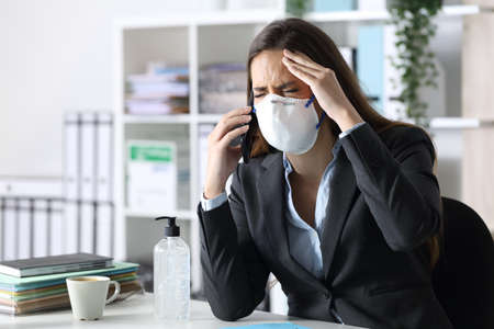 Executive woman with headache calls on smart phone wearing protective mask