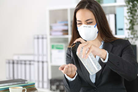 Executive woman wearing protective mask using hand sanitizer on a desk at office