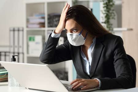 Surprised executive woman with protective mask finds mistake on laptop at night in the ofice