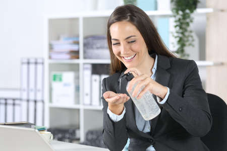Happy executive woman using hand sanitizer from bottle dispenser in the office desk