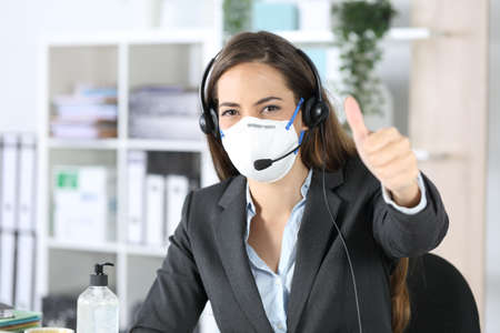Happy telemarketer woman with thumbs up looking camera avoiding covid-19 with mask sitting in the office Foto de archivo