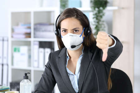 Angry telemarketer woman with thumbs down avoiding covid-19 looking camera with mask sitting in the office