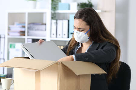 Sad fired executive woman with protective mask crying packing her stuff on a box at the office